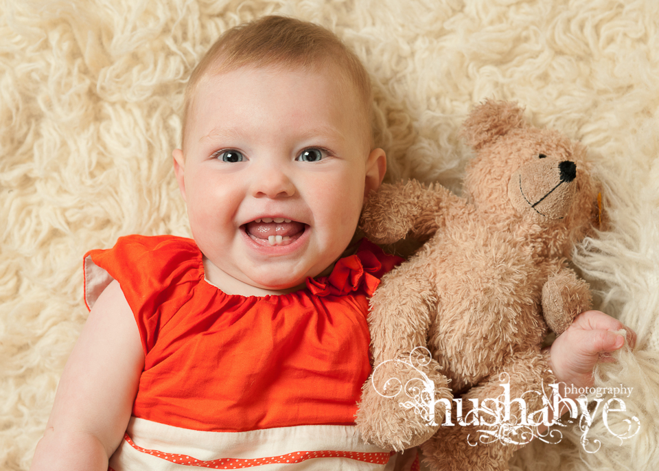 nine month old girl in orange dress cuddling teddy and smiling at the camera