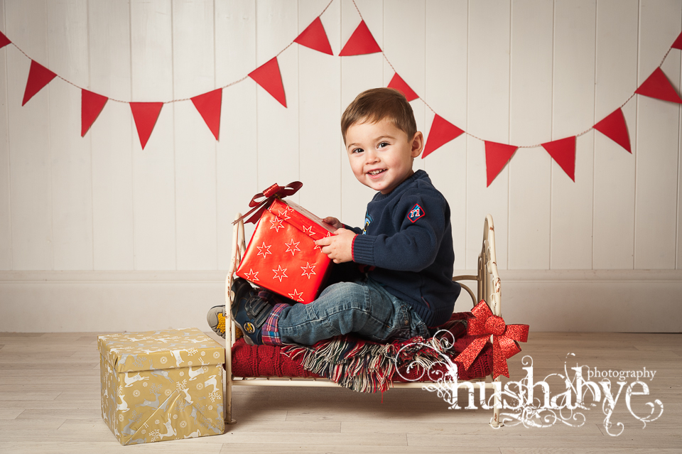 Preschool boy on mini bed with Christmas present looking happy
