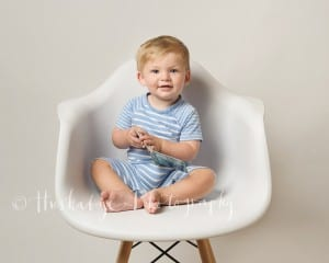 One year old boy in stripy outfit, sitting on white chair with board book