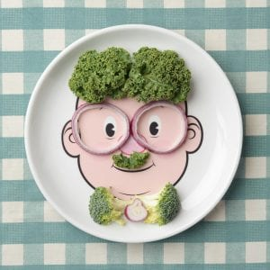 Food face plate with vegetables making his hair, moustache, glasses and bowtie