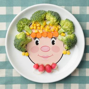 Food face plate with vegetables making her hair, necklace and earrings