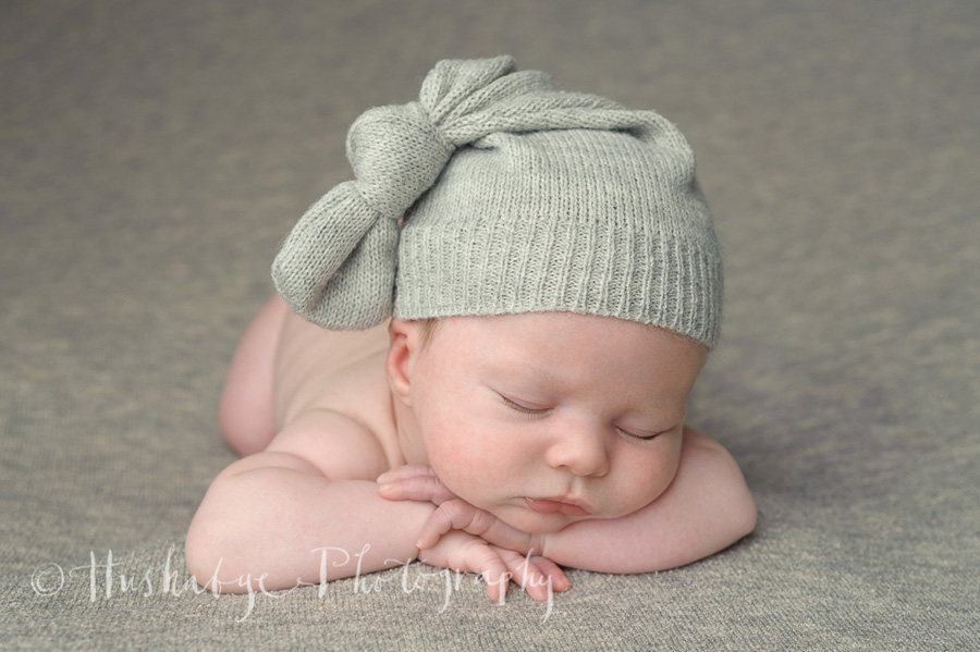 Sleepy newborn boy on grey blanket in grey woollen hat