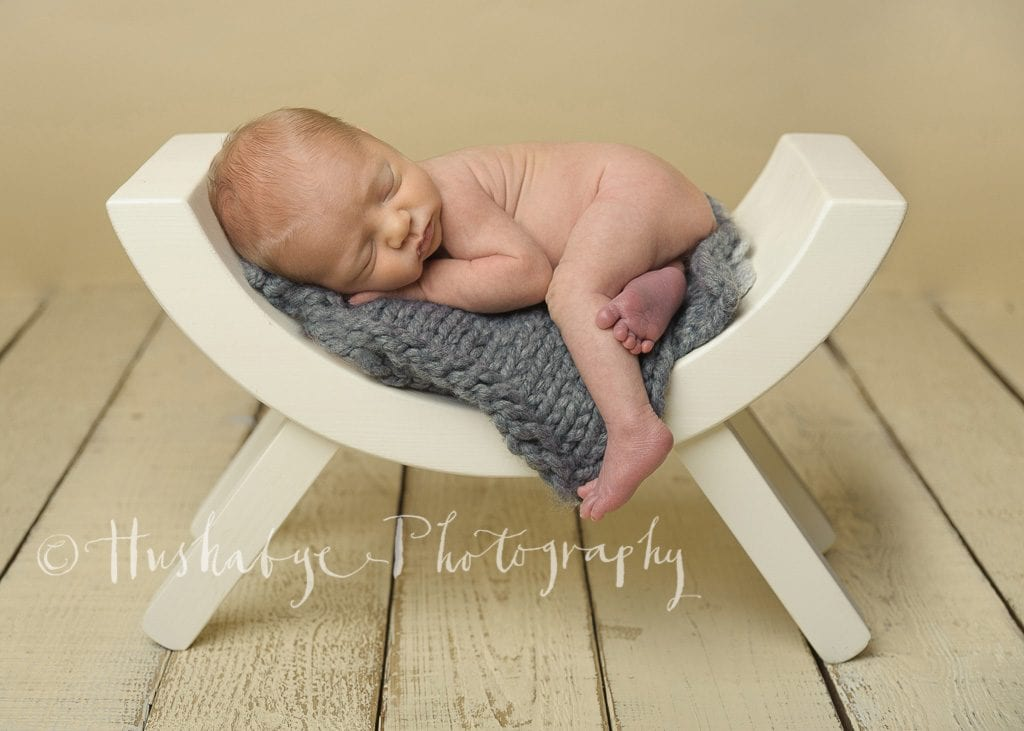 Sleepy newborn boy on grey blanket in white curved stool on cream background